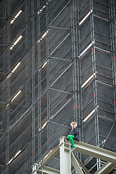 © Licensed to London News Pictures. 18/10/2019. LONDON, UK.  A climate activist (green tights) from Extinction Rebellion scales the construction scaffolding of the Queen Elizabeth Tower in Westminster.  Parliament Square and the surrounding area has been brought to a standstill as police and emergency services assess the situation.  Photo credit: Stephen Chung/LNP