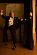 An opera singer kicks his feet up into the air while goofing around backstage.