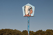 April 2021. A gas station sign painted with a portrait of a Native American chief wearing a Plains Indian headdress stands beside the abandoned Big Chief gas station on the Zia Pueblo in Northern New Mexico.
