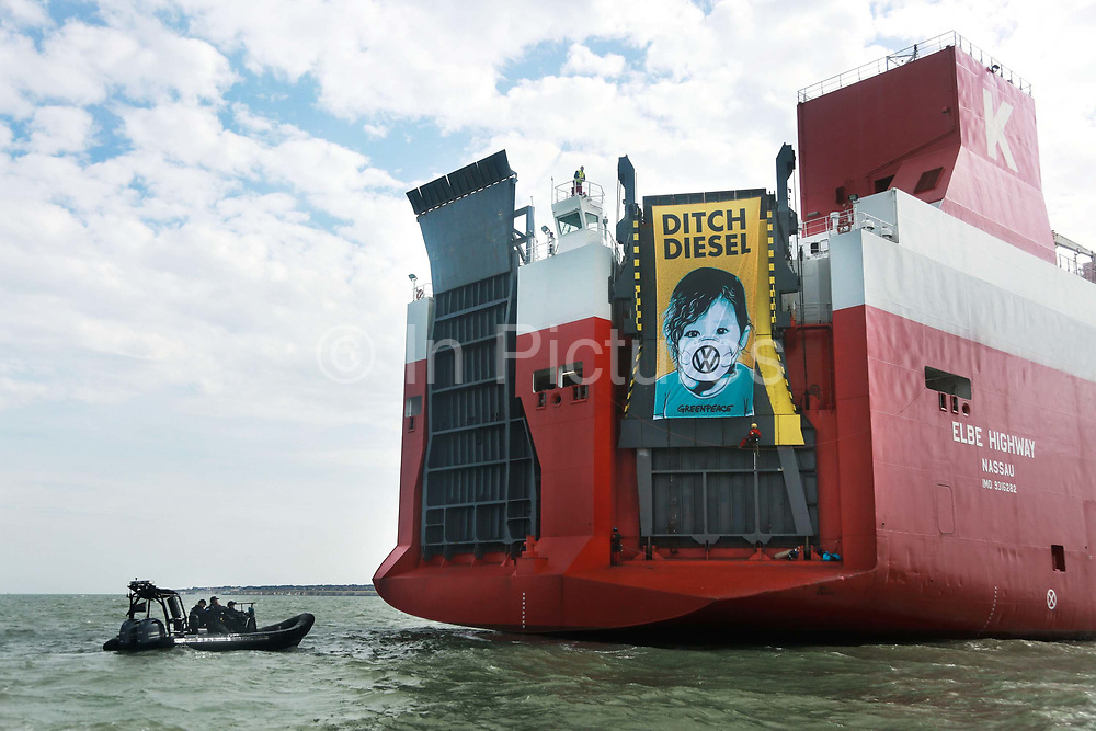 A giant banner at the back of the cargo ship calling for VW to ditch diesel September 21st 2017, Thames Estuary, Kent, United Kingdom. Greenpeace volunteers in kayaks, speed boats and climbers on the jetty prevent the 23,498-tonne cargo ship Elbe Highway from docking at Sheerness in Kent.  The cargo ship is bringing Volkswagen diesel cars into the UK and the Greenpeace action is to prevent this from happening and to make VW ditch diesel. Two climbers board the ship and hang a banner on the roll-on roll-off part of the ship preventing any cars from being off-loaded. The action is part of a long running Greenpeace campaign to curb diesel emmissions and air pollution broght on by diesel cars.