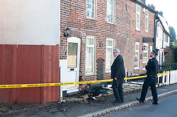 © Licensed to London News Pictures. 14/02/2019. St Pauls Cray, Structural engineer with police, A man is being hunted by police after he fled the scene of an RTC, police were called at 8.55am to reports of a car in collision with a house on Main Road, St Pauls Cray, Orpington.<br />  Local witnesses are saying the male suspect was driving his girlfriends car after an argument with her, he was also believed to have been under the influence of alcohol.  A structural engineer has inspected the property which now has a hole in the wall next to the front door, the front fence has also been distroyed.  Photo credit: Grant Falvey/LNP