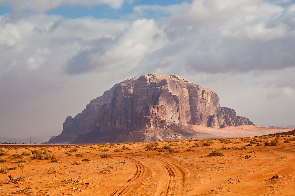 A jeep trail leads through the desert towards high sandstone cliffs in Wadi Rum, Jordan.