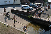 A young woman lies in shallow water after slipping on a boating ramp in Beccles Quay, on 13th August 2020, in Beccles, Suffolk, England.