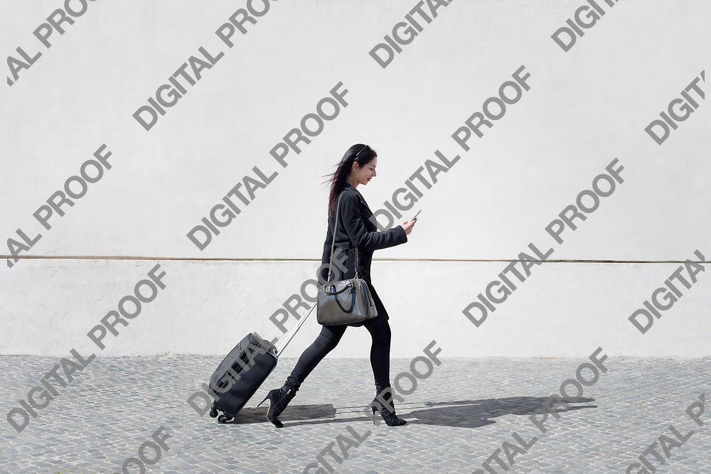 Executive and modern woman walks the street with her luggage while texting the mobile phone.