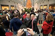tourists at the Rockefeller Center in NYC  during Christmas time making pictures of each other