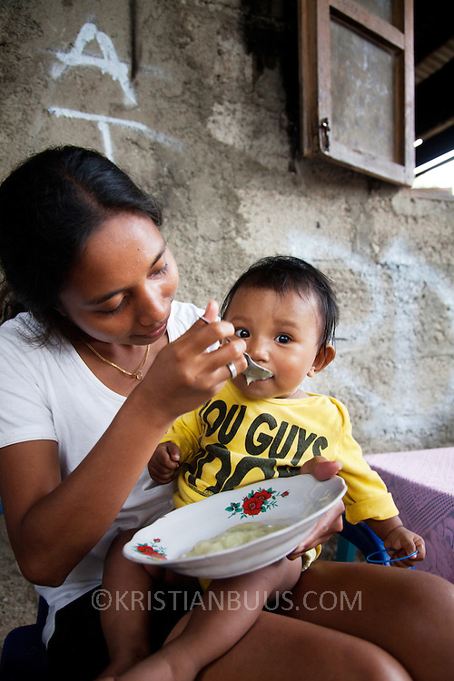 A mom is feeding her child rice mixed with meat at a Mother Support Group session where breast feeding mothers with 4 months plus babies learn about food supplements. Infant mortality rates are very high in Timor-Leste and one of the reasons for that is poor nutrition. Alola advocate breast feeding till at least two years old and teach women about nutritious supplements such as boiled and mashed rice w vegetables and eggs.  Fundasaun Alola is a not for profit non government organization operating in Timor Leste to improve the lives of women and children. Founded in 2001 by the then First Lady, Ms Kirsty Sword Gusmao, the organization seeks to nurture women leaders and advocate for the rights of women.