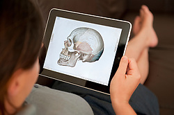 close up of woman using iPad digital tablet computer to study human anatomy using Grey's Anatomy medical app