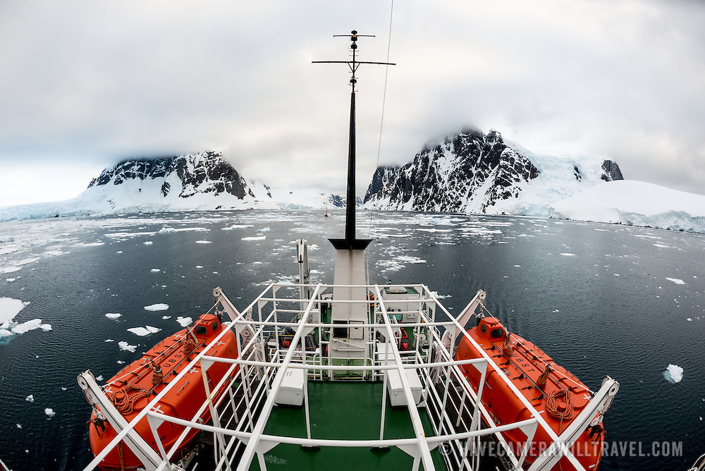 Looking back over the stern of a ship passing through calm waters in the beautiful Lemaire Channel on the western side of the Antarctic Peninsula.