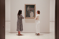"© Licensed to London News Pictures. 17/07/2019. London, UK. Staff members view Helene Schjerfbeck's painting ""Costume Picture II 1909"" at Royal Academy of Arts during the preview of her first ever exhibition in the UK. The exhibition features around 65 portraits, landscapes and still life, charting the development of Helene Schjerfbeck's work from a naturalistic style inspired by French Salon painters in the early 1880s, to a radically abstracted and modern approach from the turn of the twentieth century onwards. The exhibition runs  from 20 July to 27 October 2019. Photo credit: Dinendra Haria/LNP"