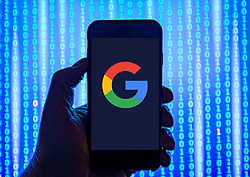 Person holding smart phone with  Google logo displayed on the screen. EDITORIAL USE ONLY