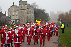 Windsor, UK. 24 November, 2019. Pikachu joins fun runners dressed as Santa Claus and his reindeer in the 2019 Windsor Santa Dash on the Long Walk in front of Windsor Castle in aid of the Alexander Devine children's hospice.