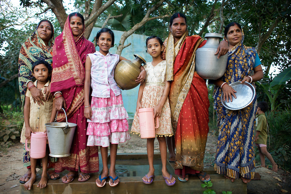 Women and children from Podumkhana village collect water from a TARA pump.  This pump was provided by UNICEF. The community is responsible for the monitoring of water quality and maintenance of the pump. The pump has a committee who fund quality control and maintenance by levying a charge of INR1 per month for each household that uses the pump. UNICEF through its partners the Ramakrishn Mission has provided training for local women so that they can undertake minor maintenance repairs to the pump and has also provided them the tools for this maintenance. The Ramakrishna Mission has provided TARA pump maintenance training for 143 groups in Purbamedinipur district. Using the local media, UNICEF have also undertaken awareness drives in this area to encourage the community to make use of water pumps and latrines. Podumkhana village has three water pumps for 238 households but suffers from poor water supply in the summer months. ..Photo: Tom Pietrasik.Podumkhana village, Purbamedinipur district, West Bengal. India.October 25th 2009