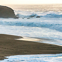 A surfer walks towards the waves at Montara State Beach near Half Moon Bay, California.