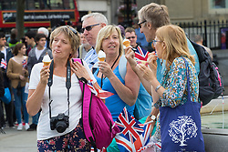 Trafalgar Square, London, June 12th 2016. Rain greets Londoners and visitors to the capital's Trafalgar Square as the Mayor hosts a Patron's Lunch in celebration of The Queen's 90th birthday. PICTURED: As the weather brightens up a group of friends enjoy an ice cream.