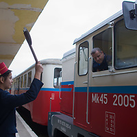 Children working at the station signal the train can leave the station of the Children's Railway in the Buda Hills in Budapest, Hungary on November 13, 2014. ATTILA VOLGYI