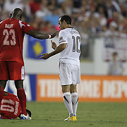 Panama defender Felipe Baloy (23) pushes away USA midfielder Landon Donovan (10) as Panama midfielder Nelson Barahona (10) lays on the ground during a  CONCACAF Gold Cup soccer match between the United States and Panama on Saturday, June 11, 2011, at Raymond James Stadium in Tampa, Fla. (AP Photo/Alex Menendez)
