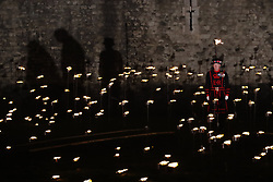 © Licensed to London News Pictures. 04/11/2018. London, UK. A Yeoman Warder stands amongst thousands of flames illuminating the moat of The Tower of London in an installation entitled 'Beyond the Deepening Shadow: The Tower Remembers'. This public act of remembrance for the lives of the fallen, honouring their sacrifice will run for eight nights, leading up to and including the Centenary Armistice Day 2018. The evolving installation will unfold each evening over the course of four hours, with the Tower moat gradually illuminated by individual flames. A specially-commissioned sound installation 'a sonic exploration of the shifting tide of political alliances, friendship, love and loss in war' will be played. At the centre of the sound installation lies a new choral work, with words from war poet Mary Borden's Sonnets to a Soldier. Photo credit: Peter Macdiarmid/LNP