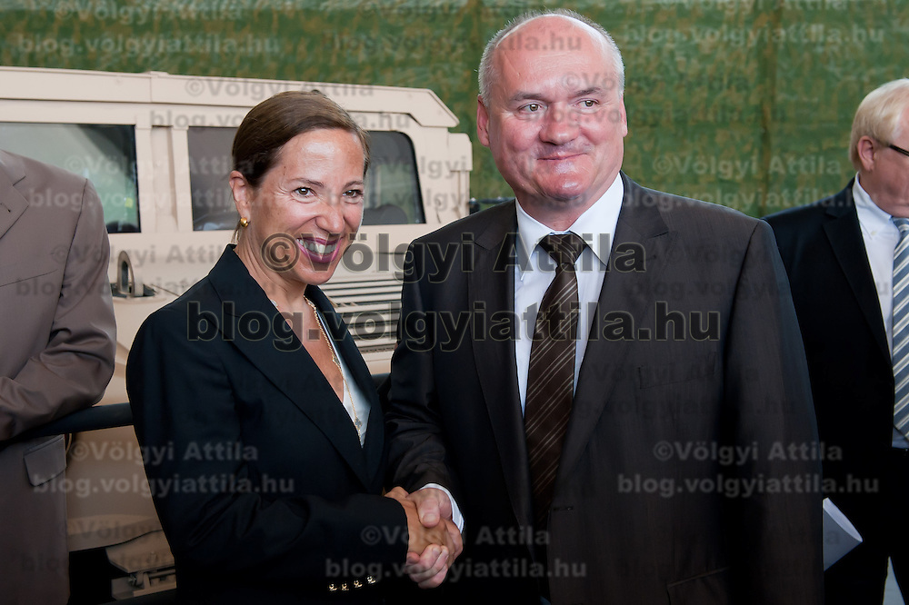 Eleni Tsakopoulos Kounalakis (L) ambassador for the United States of America and Csaba Hende (R)Defence Minister for Hungary shake hands next to a Hummer during the presentation of the Coalition Support Fund for Hungary by the US military in Szolnok, Hungary on July 18, 2011. ATTILA VOLGYI