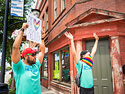 """28 JUNE 2020 - DES MOINES, IOWA: NAREN BHOJWANI and TANNER MOTE cheer during the Capitol City Pride Parade in Des Moines. Most of the Pride Month events in Des Moines were cancelled this year because of the COVID-19 pandemic, but members of the Des Moines LGBTQI community, and Capitol City Pride, the organization that coordinates Pride Month events, organized a community """"parade"""" of people driving through the East Village of Des Moines displaying gay pride banners and flags. About 75 cars participated in the parade.    PHOTO BY JACK KURTZ"""