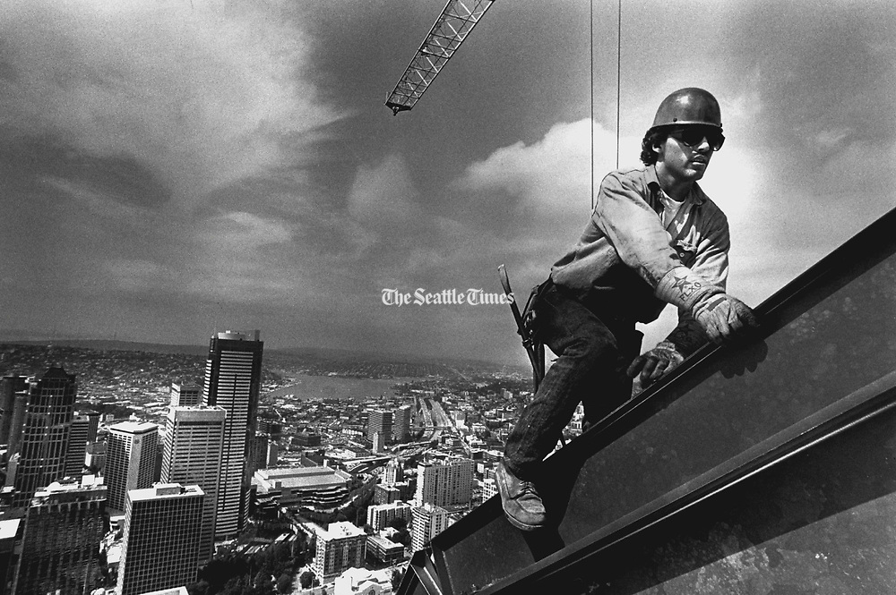 An Iron worker climbs the outside steel beam at the very top of the AT&T Gateway Tower. The 62-story view behind him looks North with downtown Seattle in the foreground. (Greg Gilbert / The Seattle Times, 1989)