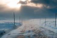 Stormlight as a spring blizzard brings rapidly drifting show over Hardangervidda northern (E7) road (which runs across the north of the Hardangervidda plateau)