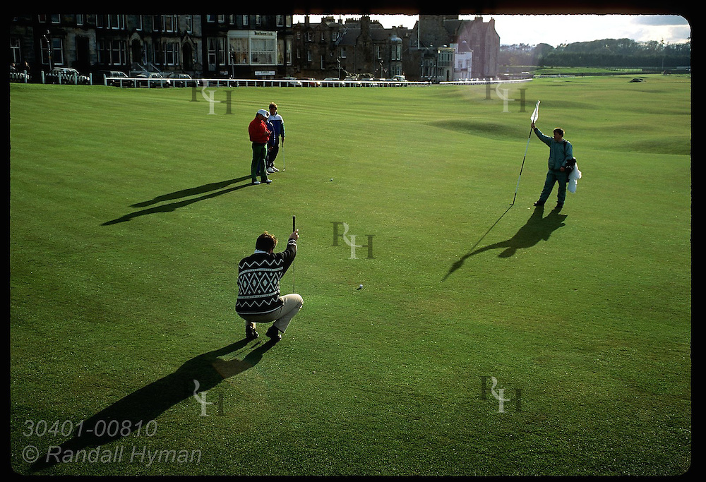 Man lines up his putt on green of the eighteenth hole of the Old Course at St. Andrews Links. Scotland
