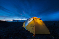 warm glow coming from inside a North Face tent while camping along the rugged coastline of Jokulsarlon, Iceland