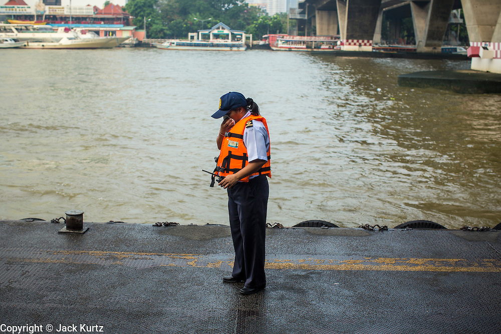 21 NOVEMBER 2012 - BANGKOK, THAILAND: A safety worker in a life preserver waits for a Chao Phraya Express boat at Sathorn Pier in Bangkok. The Chao Phraya Express boats run up and down the Chao Phraya River in Bangkok providing a sort of bus service for neighborhoods near the river. The boats are the fastest way to get from north to south in Bangkok. Thousands of people commute to work daily on the Chao Phraya Express Boats and fast boats that ply Khlong Saen Saeb. Boats are used to haul commodities through the city to deep water ports for export.    PHOTO BY JACK KURTZ