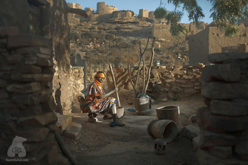 A woman pounds millet in a courtyard, Niongono, Dogon Country, Mali.