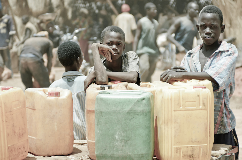 Stock photograph of African boys with jerrycans of water used to wash the crushed ore and extract gold using gravity separation techniques.