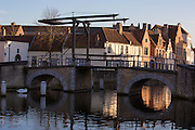 Late afternoon sun shines on buildings along a canal near a swing bridge, in Bruges