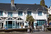 People sitting outside The Rising Sun pub, St Mawes, Cornwall, England, UK
