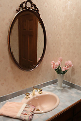 A modern bathroom with a tiled counter top, mirror, vase of silk flowers, ceramic soap dispenser and cup, backsplash and a gold handled faucet set with a dusty rose colored sink