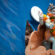 A young man looks through a tear in the blue  tarpauline sheet covering the truck transporting an idol of lord Ganesh for immersion in the Indian ocean on the last day of the Ganesh Chaturthi festival. Ganesh, the elephant-headed son of Shiva and Parvati is widely worshiped as the supreme God of wisdom, prosperity and good fortune. Mumbai, September 2009.
