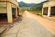 14 MARCH 2013 - ALONG HIGHWAY 13, LAOS: A road going past deserted buildings leading to an abandoned Chinese hotel near the end of Highway 13 in the Boten Special Economic Zone. The SEZ is in Laos immediately south of the Lao Chinese border. It has turned into a Chinese enclave but many of the businesses struggle because their goods are too expensive for local Lao to purchase. Some of the hotels and casinos in the area have been forced to close by the Chinese government after reports of rigged games. The paving of Highway 13 from Vientiane to near the Chinese border has changed the way of life in rural Laos. Villagers near Luang Prabang used to have to take unreliable boats that took three hours round trip to get from the homes to the tourist center of Luang Prabang, now they take a 40 minute round trip bus ride. North of Luang Prabang, paving the highway has been an opportunity for China to use Laos as a transshipping point. Chinese merchandise now goes through Laos to Thailand where it's put on Thai trains and taken to the deep water port east of Bangkok. The Chinese have also expanded their economic empire into Laos. Chinese hotels and businesses are common in northern Laos and in some cities, like Oudomxay, are now up to 40% percent. As the roads are paved, more people move away from their traditional homes in the mountains of Laos and crowd the side of the road living off tourists' and truck drivers.    PHOTO BY JACK KURTZ