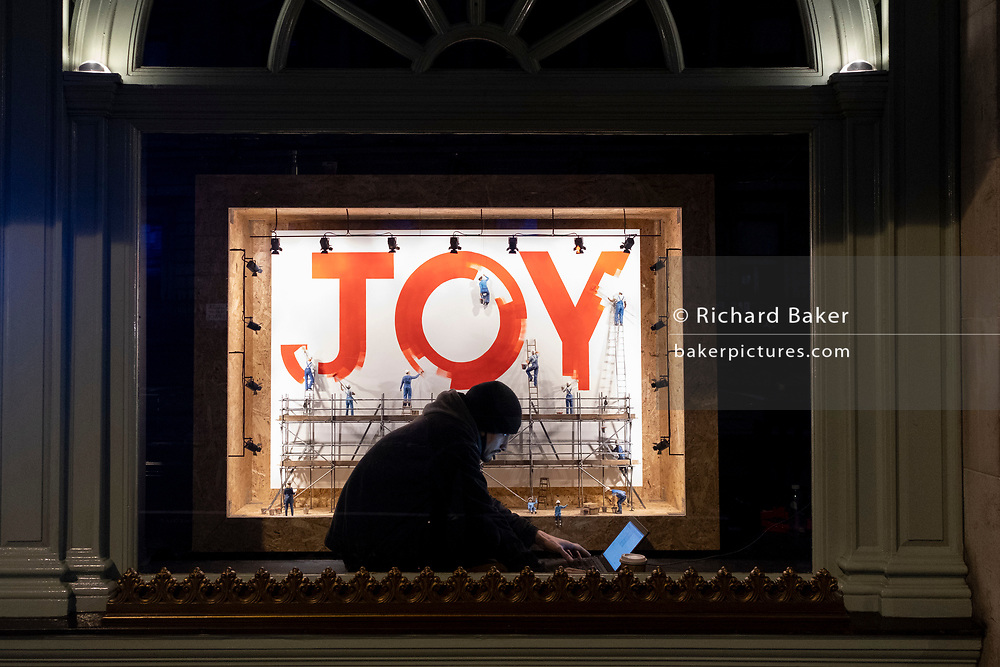 """Sitting in front of a window display, a young man watches the screen of his laptop in the window of Fortnum and Mason on Piccadilly which features an instillation by the artist and theatre designer, Alex Berry, on 2nd February 2021, in London, England. Writes Berry in the window: """"These tiny people working together to paint their big message is a tribute to the power of community and to all the people who work behind the scenes to bring joy into our lives,"""""""