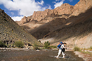 Liana Welty wades across a river in the Tessaout Valley, M'Goun Massif, Central High Atlas, Morocco.