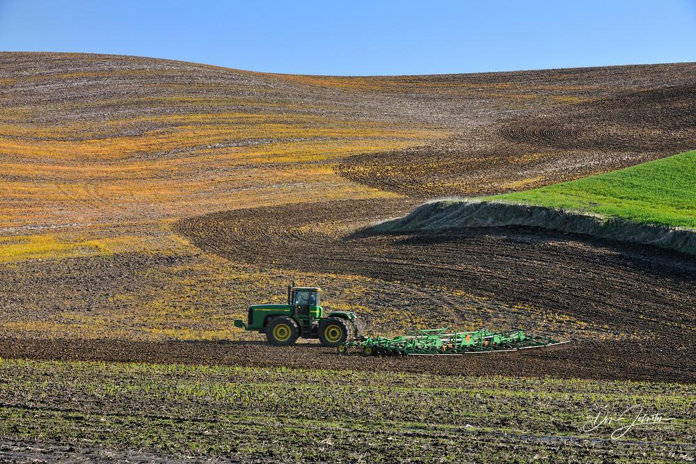 Farm tractor preparing Palouse farmland in spring, near Pullman, Washington, USA