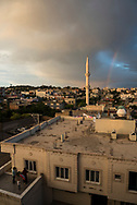 A rainbow arches through the sky at sunset in Midyat, Turkey. In the bottom left, two women finish grilling food in preparation for the day's iftar meal. (June 1, 2017)