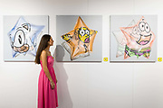 A woman views star artwork from Five Stars by Fanakapan at the preview of Moniker Art Fair on October 04, 2018, taking place during Frieze Week at the Old Truman Brewery in London, England. The art fair embraces contemporary urban art from emerging and established artists and this year, the shows theme is Uncensored, shedding light on social, economic and ecological issues.