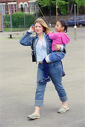 Single mother walking across primary school playground carrying young daughter,