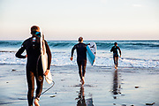Father and sons holding surfboards, running into the waves and surf at St Ouen's Bay, Jersey at sunset.