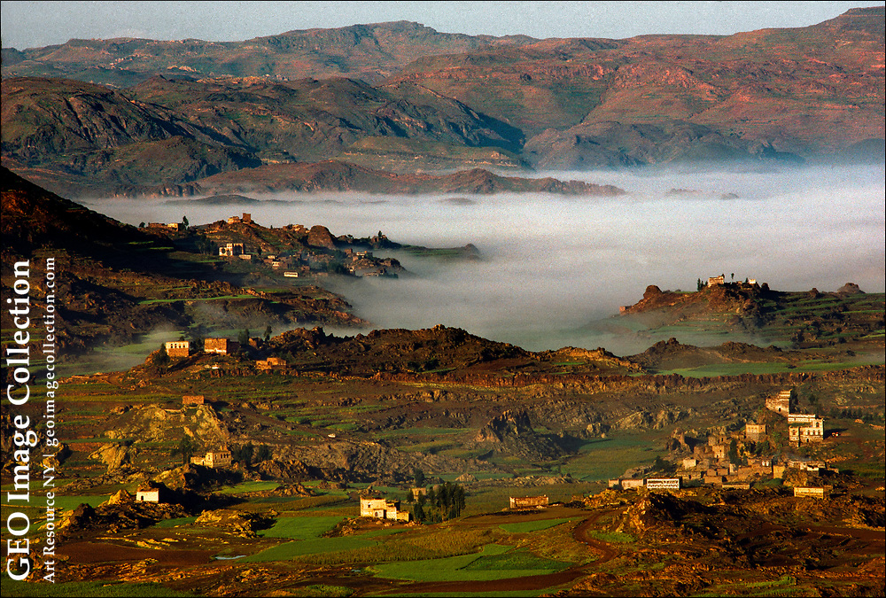 Near Dhamār in the Yemen highlands, fog shrouds the fertile, terraced fields of a 12 mile wide valley situated between two volcanic peaks. Dhamār was the seat of a renowned madrasah or theological school for the Zaydi sect of Islam, which was dominant for many centuries.