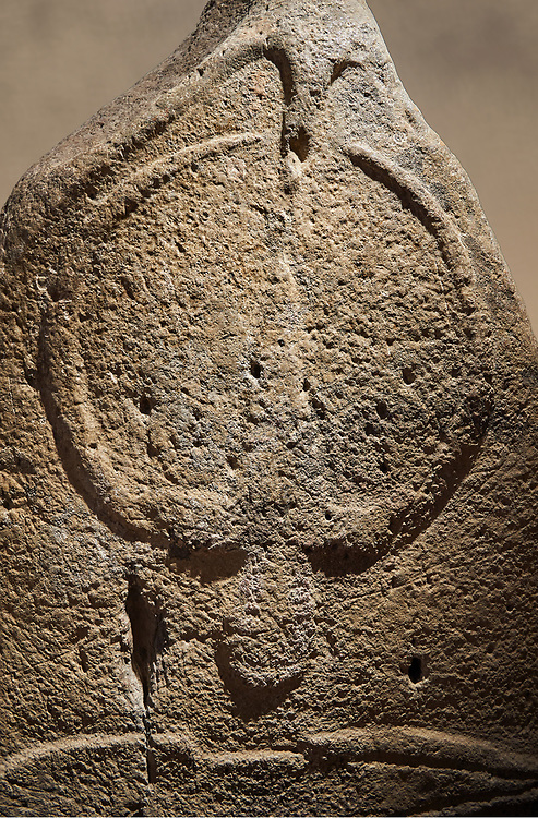 Late European Neolithic prehistoric Menhir standing stone with carvings on its face side. The representation of a stylalised male figure starts at the top with a long nose from which 2 eyebrows arch around the top of the stone. below this is a carving of a falling figure with head at the bottom and 2 curved arms encircling a body above. at the bottom is a carving of a dagger running horizontally across the menhir. From Barrili I site, Laconi. Menhir Museum, Museo della Statuaria Prehistorica in Sardegna, Museum of Prehoistoric Sardinian Statues, Palazzo Aymerich, Laconi, Sardinia, Italy. Warm art background. .<br /> <br /> Visit our PREHISTORIC PLACES PHOTO COLLECTIONS for more  photos to download or buy as prints https://funkystock.photoshelter.com/gallery-collection/Prehistoric-Neolithic-Sites-Art-Artefacts-Pictures-Photos/C0000tfxw63zrUT4
