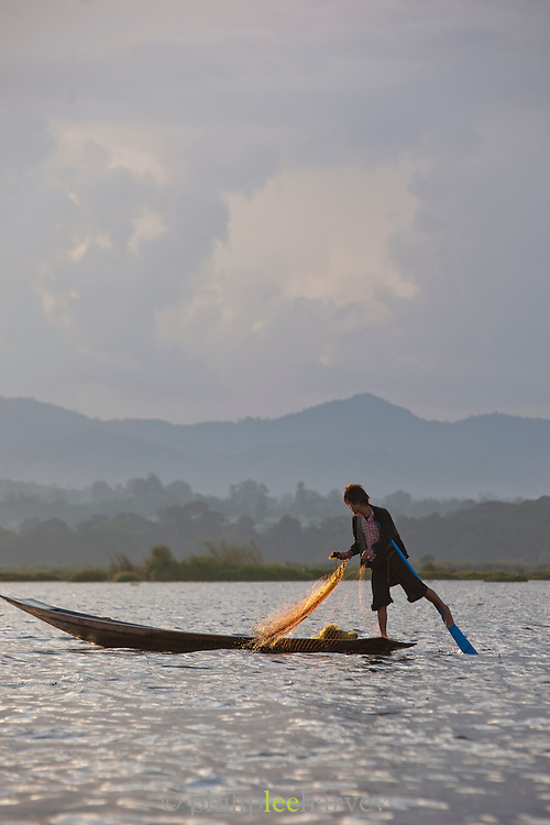 A fisherman rowing with his legs to keep his hands free to fish with a net, on Inle Lake, Myanmar