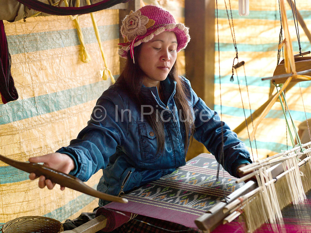 A Lao Phong woman weaves fabric using the 'mutmee' tie-dye weaving technique, in Ban Saleuy, Houaphan province, Lao PDR. Ikat, called mutmee or matmee in Lao, is the Malay word for tie. Threads are tied to resist the dye, then coloured in the dyebath to pattern them before being woven as plainweave. The colours on the fabric blur at the edges like tie-dye.