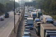 Traffic builds up on the M25 between Junctions 9 and 10 after Insulate Britain climate activists block the clockwise, and then anticlockwise, carriageway as part of a campaign intended to push the UK government to make significant legislative change to start lowering emissions on 21st September 2021 in Ockham, United Kingdom. The activists are demanding that the government immediately promises both to fully fund and ensure the insulation of all social housing in Britain by 2025 and to produce within four months a legally binding national plan to fully fund and ensure the full low-energy and low-carbon whole-house retrofit, with no externalised costs, of all homes in Britain by 2030.