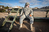 328th MP, PFC Lippincott, a National Guardsman with a company based out of Cherry Hill, rides in the back of a military truck and surveys the destruction.