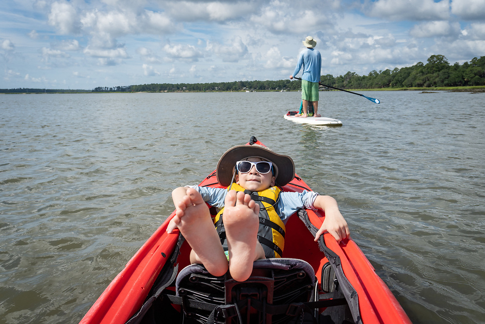 Sam relaxes in the bow of a double kayak as he, Eleanor and Michael return to Palmetto Bluff from swimming at an upriver sand bar.