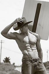 shirtless muscular cowboy leaning against a sign post outdoors